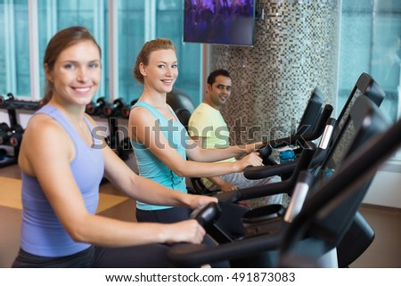 Three Sporty People Cycling Exercise Bikes in Gym