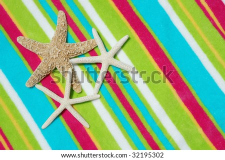 Three starfish on a colorful beach towel
