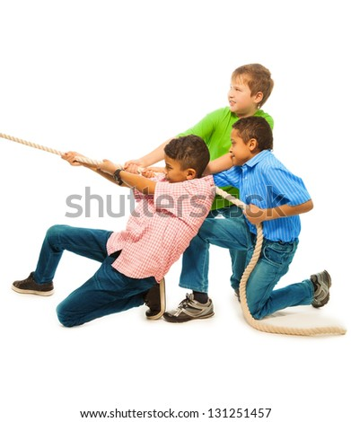 Three strong boys pulling the rope with strength standing isolated on white