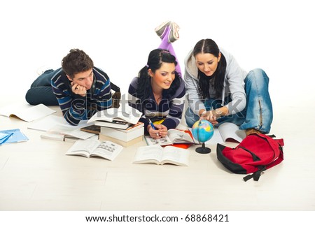 Three students lying on wooden floor making homework and  looking on world globe  together