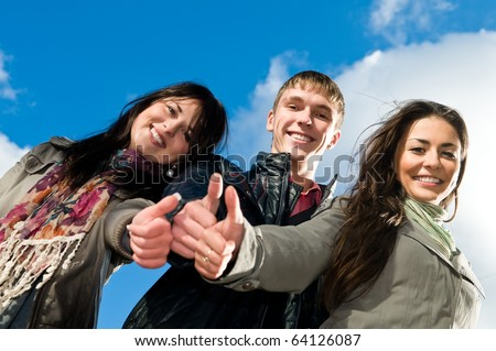 Three students standing over blue sky with thumbs up. Lower point of view