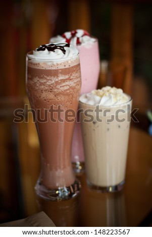 Three tall glasses of iced drinks, smoothies and coffee