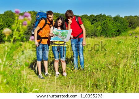 Three teenagers with backpacks looking at the tour map