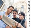 Three tourist looking at map - stock photo