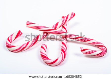 three twisted red and white candy canes on a white background