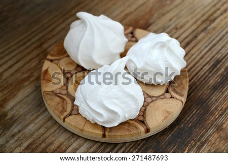 Three white bizet cookies on wooden table