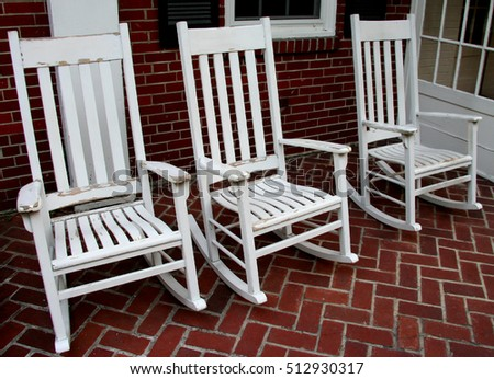 Three White Rocking Chairs On Brick Porch
