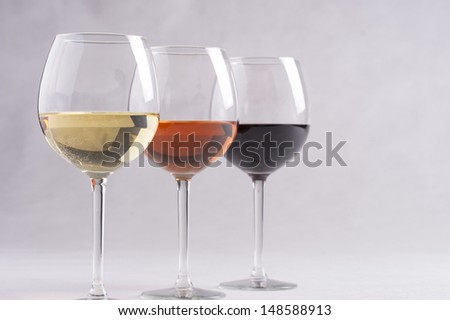 Three wine glasses with different wines - red, rose and white on a solid background