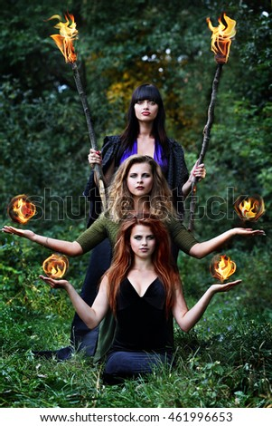 three witches are holding balls of fire