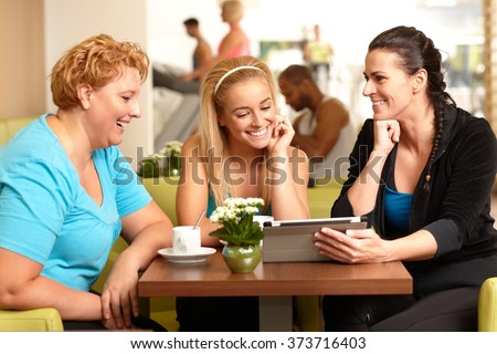 Three women sitting around coffee table in gym, talking, looking at photos on tablet computer.