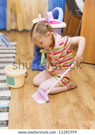 three year old girl sweeping the floor in her room