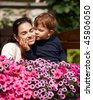 Three years old kid kissing happy mother outdoor in spring garden, smiling. - stock photo