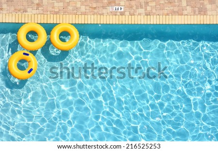Three yellow pool rings floating in a swimming pool, room for your text