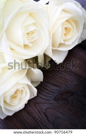 Three yellow roses on a wooden background.