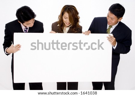 Three young business people look at a large blank white space