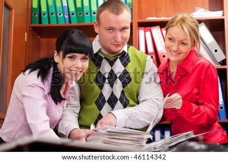 Three young coworkers doing paperwork