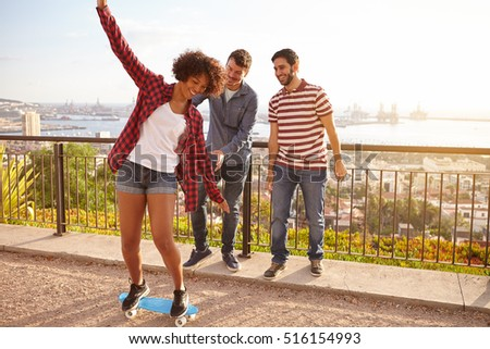 Three young friends playing with a skateboard on a bridge, all laughing while the girl is keeping her balance on the skateboard