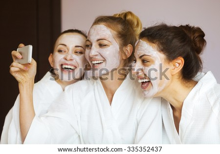 Three young happy women with face masks taking selfi at spa resort. Frenship and wellbeing concept