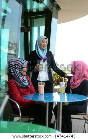 Three young pretty Asian muslim business woman in head scarf drink at cafe