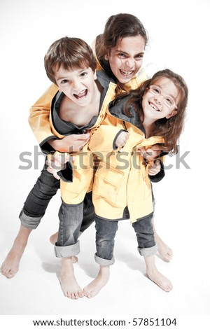 Three young siblings barefoot wearing jeans and yellow raincoats