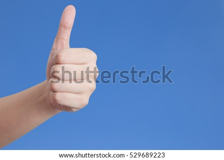 Thumb up isolated on blue background.