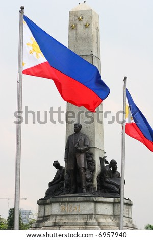 Tight shot of the Rizal monument at Luneta with Philippine flags