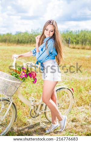 time for cycling fun: portrait of beautiful brunette young woman having fun relaxing with bicycle on summer green field and blue sky outdoors copy space