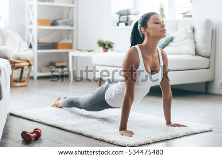Time for yoga.  Attractive and healthy young woman doing exercises while resting at home