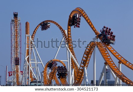 Time-laps of the twist and turns of a modern roller coaster with the cars in different locations. Motion blur on cars and people