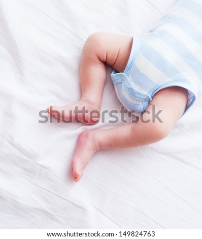 Tiny feet of newborn baby. Legs newborn baby.