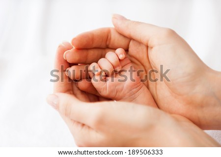 Tiny little hand. Close-up of father holding a tiny hand of his little baby