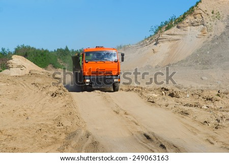 Tipper dumptruck carrying sand to a building site