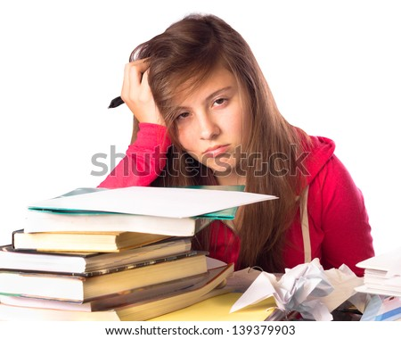 Tired and stressed teenage girl surrounded by books doing homework