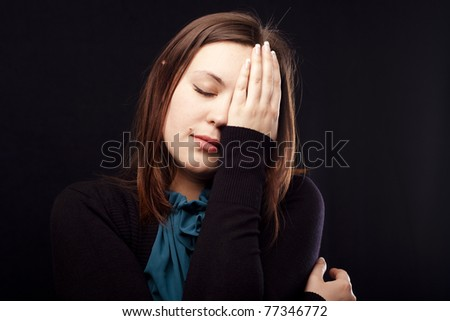 Tired lady covering her face with hand.