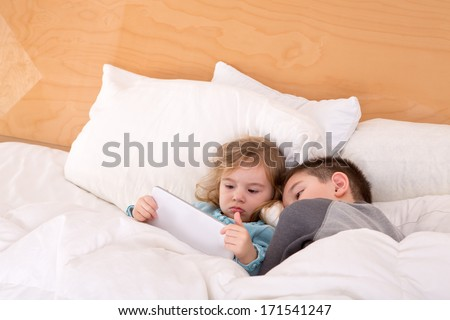 Tired little brother and sister snuggling up together in a warm comfortable bed as they read a bedtime story on a tablet computer before falling asleep