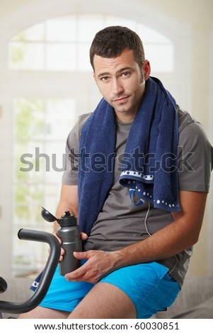 Tired man sitting on stationary bike and resting after training.