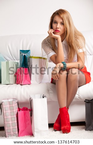 Tired woman returning after shopping sits on sofa at home