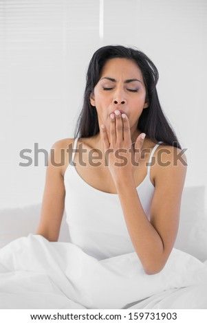 Tired yawning woman sitting on her bed in bright bedroom