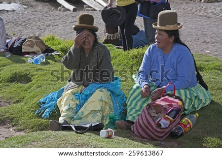 Titicaca lake, Bolivia - January 2: Bolivian women chew coca while waiting for  ferry Copacabana, Bolivia on January 2,2009. Chewing coca is legal in Bolivia.