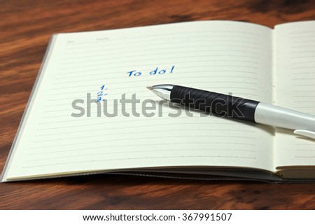 To do list  with a pen on wood table