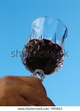 toasting with red wine glass isolated against blue