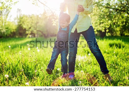 Toddler boy and his mom having fun in summer park, Image with backlight, some stay light in foreground