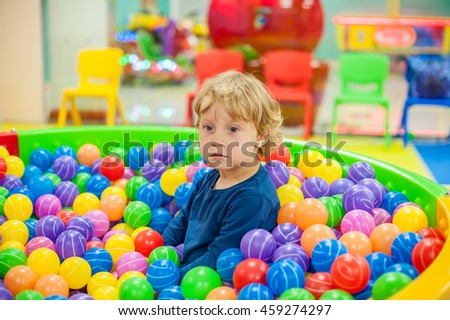 Toddler boy sits in the balls in the game room