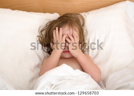 Toddler Girl closing her eyes in the bed, perhaps she is seeing bad dreams.