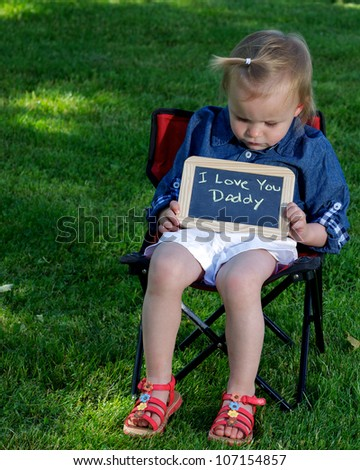 Toddler sitting outside looking at a sign she is holding that say�s �Daddy I Love You�.