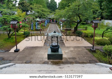 Tokyo, Japan - August 29, 2016: Looking down the alley and park of Ryodaishi temple of Two Saints at Ueno park. Text on banners praises The God Guardian