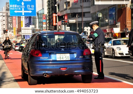 TOKYO, JAPAN - DECEMBER 6, 2009_Police tickets driver on the street in Tokyo, Japan.