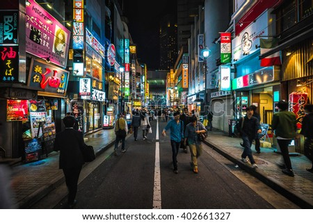 TOKYO - MAY 16, 2014: People walk in the night on the walking street of Shibuya district in Tokyo, Japan