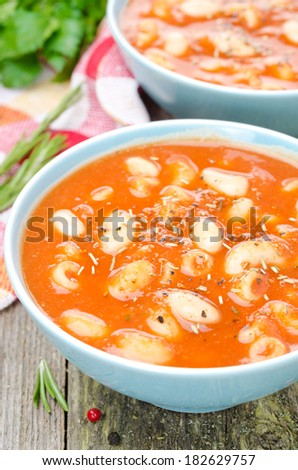 tomato soup with pasta, white beans and rosemary, close-up top view ...