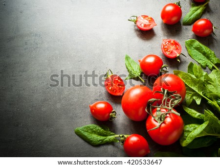 Tomatoes and spinash at slate background with space for text. Healthy eating and Diet concept.  Vegan food background.